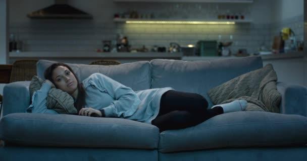 Nyugodt nő feküdt egy hangulatos nappaliban kanapé este tv nézés.