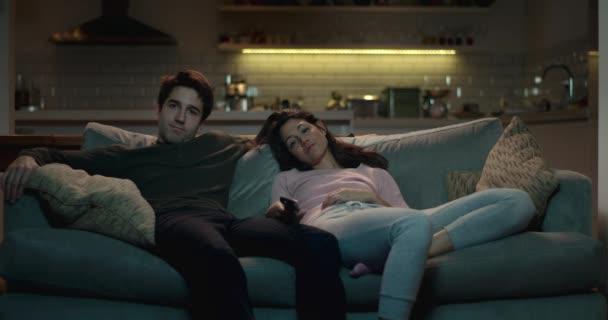 Uvolněná pár propadu na gauči v útulném obývacím pokoji dívat na televizi.