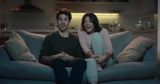 Pár na pohovce reagují v úžasu na něco v televizi.