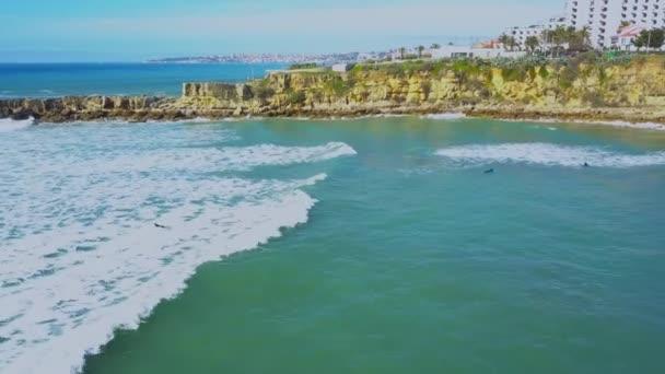 Letecký pohled na pobřeží Atlantiku a surfaři ve vodě a na vlnách v Cascais v Portugalsku. Clifs pobřeží a moře