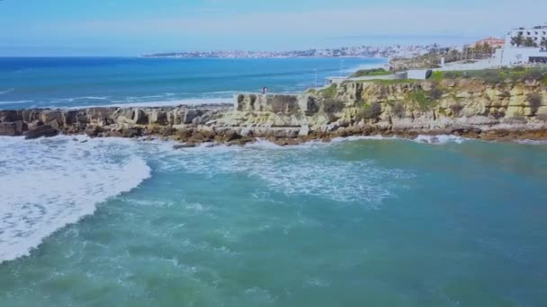Aerial View of Atlantic coast and surfers in water an on the waves in Cascais, Portugal. Clifs coast and sea