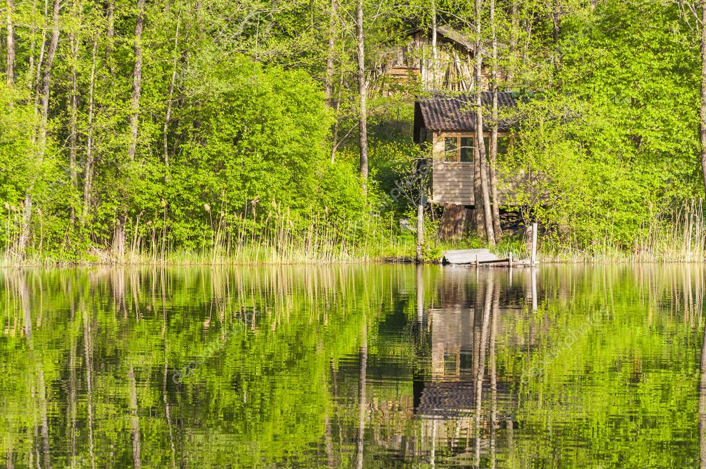 Abandoned obsolete rural wooden house on lake coast. Small wooden house ruins in rural abandoned Lithuanian village. People born live and die build a shelter and leave it for a reason and without.