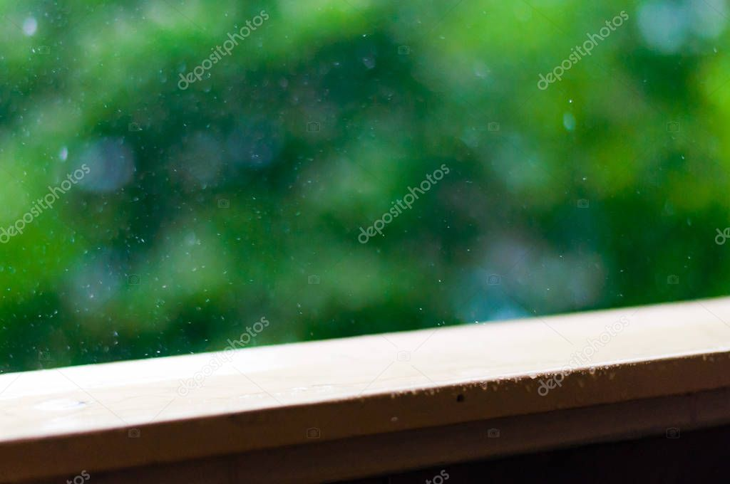 Summer rain raindrops falling down on wooden painted handle of balcony railings on blurred trees background