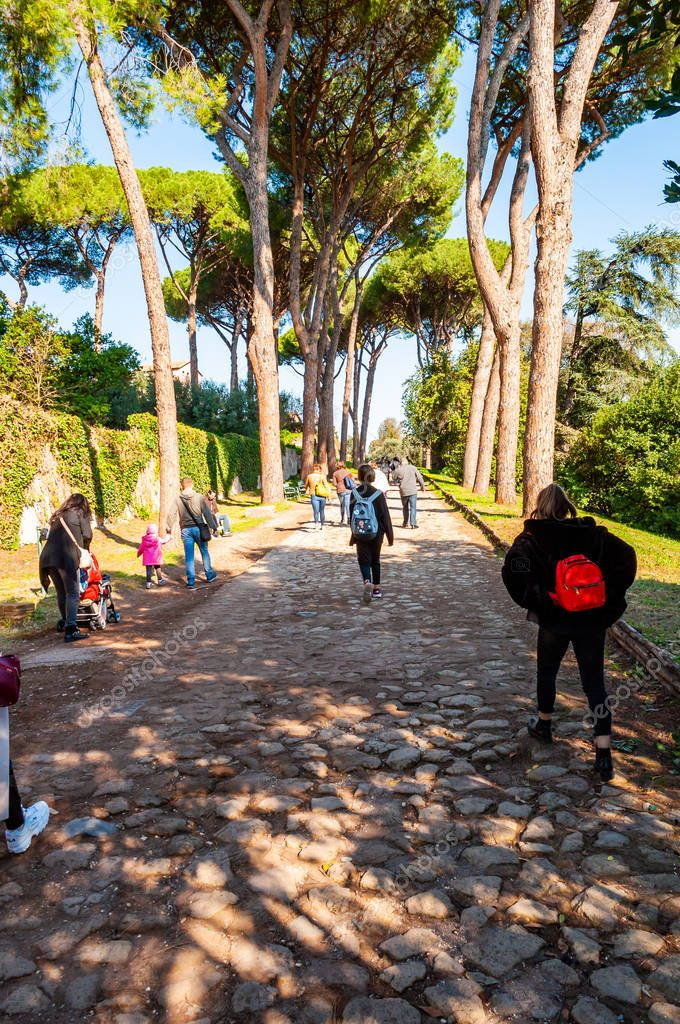 Rome, Italy - November 17, 2018: Scenic evergreen park with growing pines, velvet grass lawns, cozy walkways in between the trees with walking people up the Palatine hill in Rome
