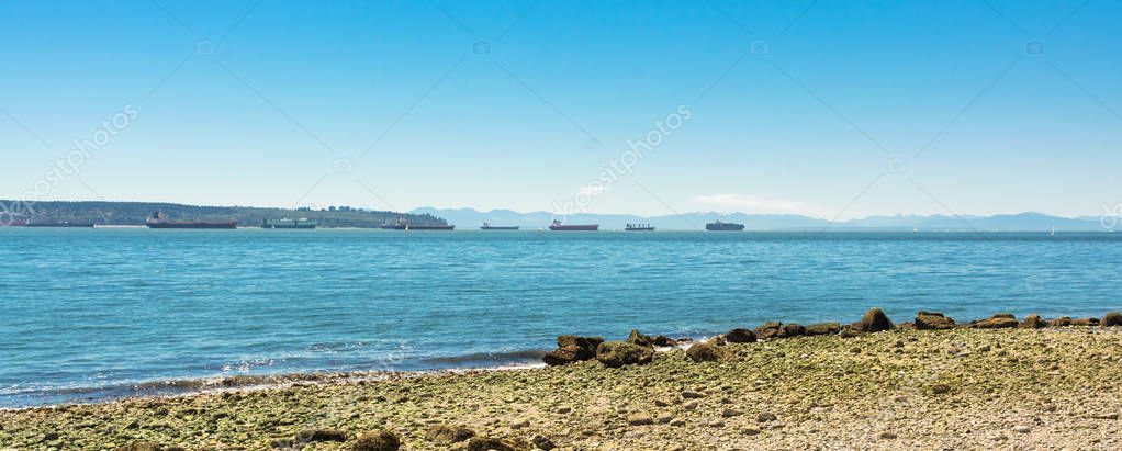 Seagoing vessels passing a harbor. Ship traffic from a port