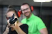 Střelnice. Žena střílí ze zbraně na střelnici pod dohledem instruktora.