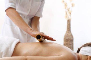 Relaxing bamboo massage. The masseur massages the body using bamboo sticks.