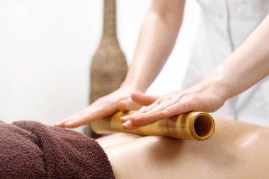 Massage with bamboo sticks. The masseur massages the body using bamboo sticks.