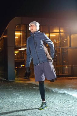 Running on snow. The man is training the night in the city.