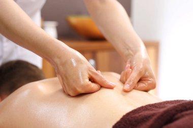 Back massage. The masseur massages his back.
