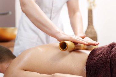 Back massage.The masseur massages the body using bamboo sticks.