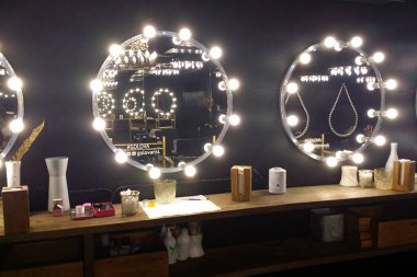 Atmospheric black interior in the beauty salon. Mirrors with light bulbs. Place for make up.