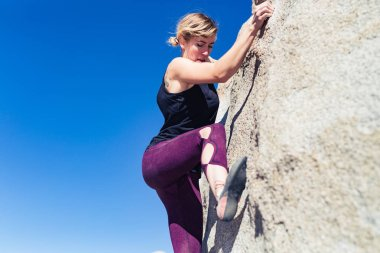 Thin blonde caucasian woman wearing black tank top rock climbing on boulders in the desert of California on a bright sunny day