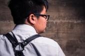 Junge Transgender Mann in halb formale Kleidung mit Leder Fesselharness Stil stellt in einer trashigen städtische Lage