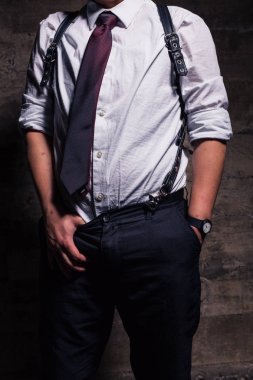 Young transgender man in semi formal clothing with a bondage style leather harness poses in a grungy urban location