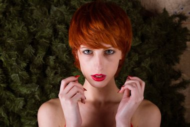 tall fit caucasian woman with short red hair looks expectantly at the viewer in front of a pine wreath with holiday colors