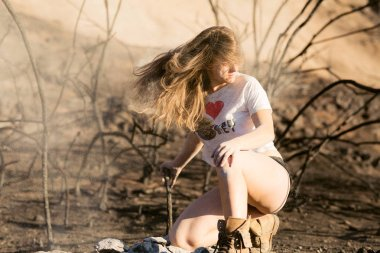 Young mixed race woman in white shirt and short shorts playing with hair near forest destroyed by wildfire while covered in ashes