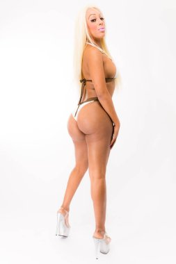 Fit young black  woman with long blonde hair poses in a white two piece and high heels against a white background
