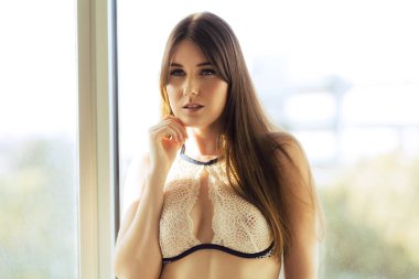 Attractive Caucasian woman with long straight hair wearing white sheer fabric poses in front of window