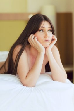 Attractive Caucasian woman with long straight hair wearing white sheer fabric poses on bed