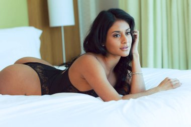 Attractive Indian woman in black lingerie poses against a floor length window in natural light