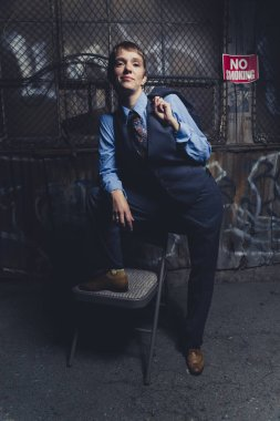 Queer woman dressed in suit and tie poses in a grungy industrial location