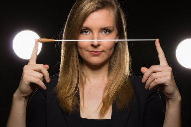 Young caucasian woman conductor poses with baton in a dark space with stage lights
