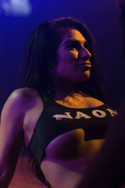 Fit young hispanic woman in black two piece outfit dances at a nightclub with colored lighting and a stage with pole.
