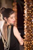 Mladá Kavkazský žena oblečená jako Audrey Hepburnová pózy v místnosti plné světýlka