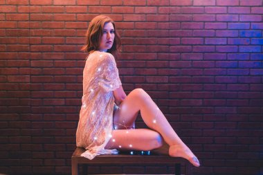 Young caucasian woman in sheer dress poses with string lights against a brick wall