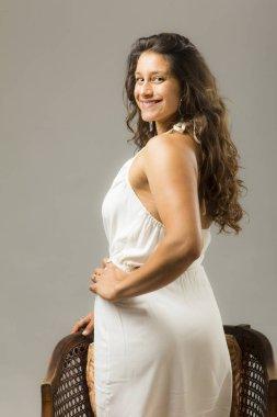 young beautiful woman posing in studio wearing white dress