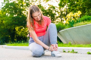 A jogger has injured her ankle during sports and holds it tight