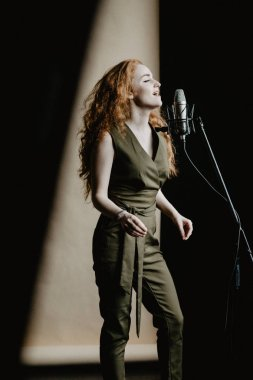 Beautiful singing girl with microphone in studio