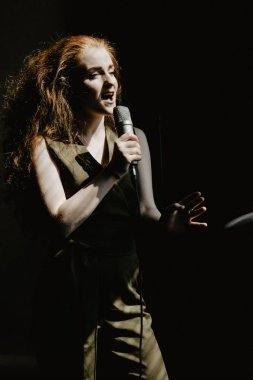 Singer with microphone on the black background
