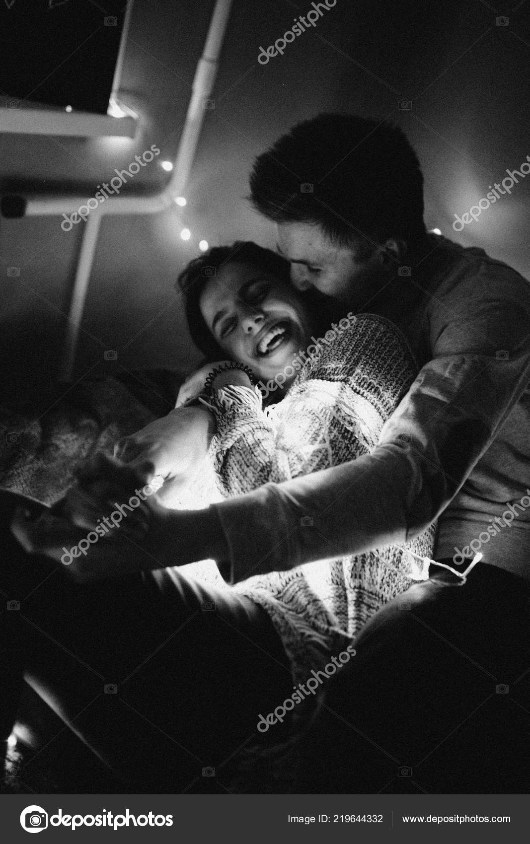 Loving couple hug each other on the bed wrapping in garland in bedroom black and white photo with noise filter photo by