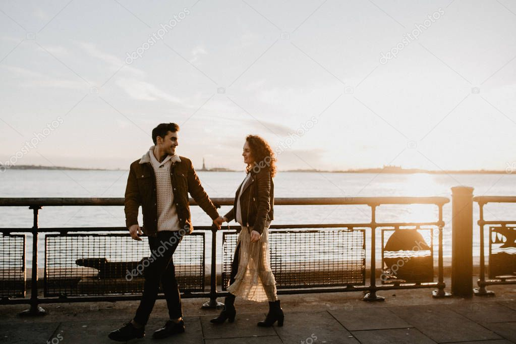 Outdoor smiling couple in love posing at sunset, wearing stylish retro outfits. Romantic mood and atmosphere