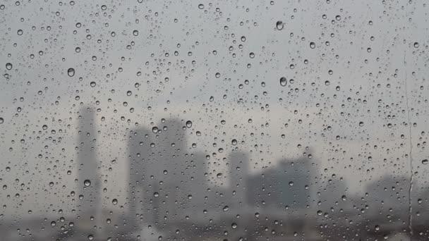 Kapky deště proudí skrz skleněné okno, silueta města, dešťové kapky na okno