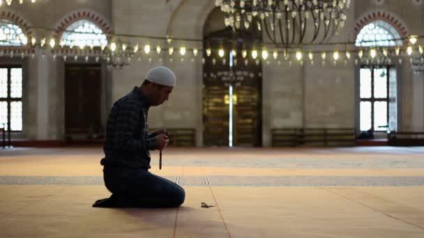 junger erwachsener kaukasischer Mann in der Moschee, Anbetung mit Gebetsperlen oder Rosenkranz