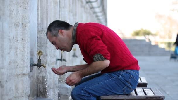 Muslim man taking ablution for prayer