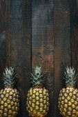 Fotografie Ripe pineapples border frame on dark wooden vertical background. Tropical fruit creative concept. Empty space for copy, text, lettering.