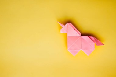 Handmade pink trendy geometrical polygonal paper origami unicorn on blue background. Empty space. Horizontal poster, postcard, banner template.