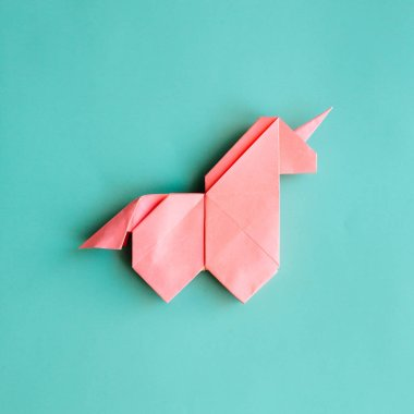Handmade pink trendy geometrical polygonal paper origami unicorn on blue background. Empty space. Square poster, postcard, banner template.