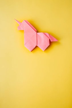 Handmade pink trendy geometrical polygonal paper origami unicorn on blue background. Empty space. Vertical poster, postcard, banner template.
