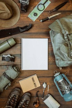 Camping gear including knife, clothes, boots, lantern, camera, hat, map, compass. Vertical wanderlust, safari postcard, poster, banner template. Empty notepad space for text,copy, lettering.