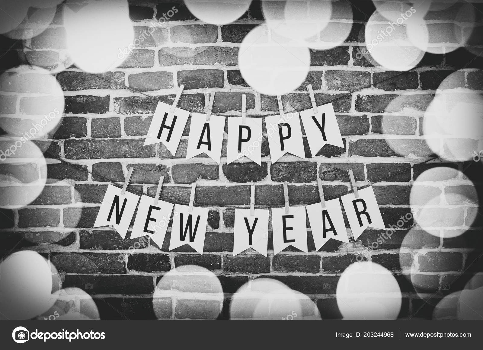 black and white happy new year text lettering paper card homemade flag garland with blurred lights border decoration on aged retro brick wall background