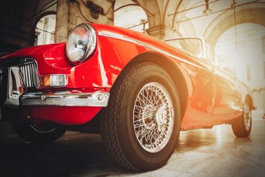 Front view of red shiny classic vintage car. Retro toned postcard, poster.