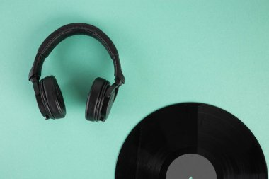 Vinyl record and headphones on abstract pastel background with copy space flat lay