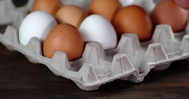 Mužská ruka vezme syrová vejce z kazety.