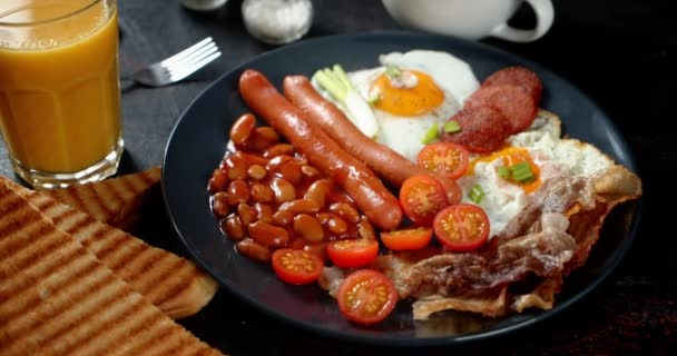 English Breakfast of eggs, beans and sausage on the plate.