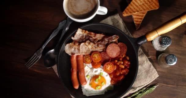 Anglická snídaně v pánvi na stole se pomalu otáčí.